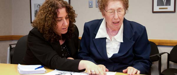 A social worker at the Cummings Centre in Montreal assists a Nazi victim with her compensation application